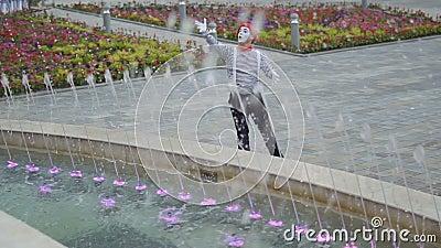 Grappig boots beweging zijn handen als leider na en controleer de fonteinen stock footage