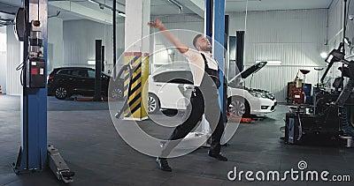 Grappig en opgewonden mechanisch dansen voor de camera in een groot servicecentrum stock videobeelden