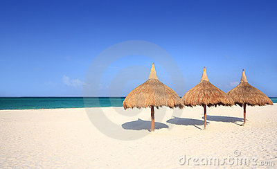 Thatch palapa umbrellas on resort beach