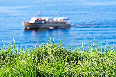 Grass with seas and boat on background