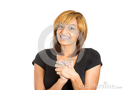 Grateful happy young woman with hands clasped close to chest