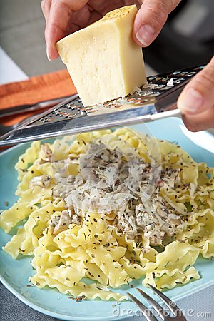 Grating cheese on pasta