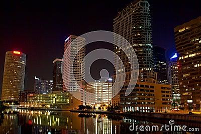 Grattacieli alla notte lungo il canale navigabile
