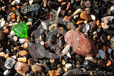 Gravel on a beach with a green glass fragment