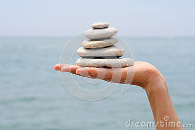 Gravel pile in woman s hands with sea background