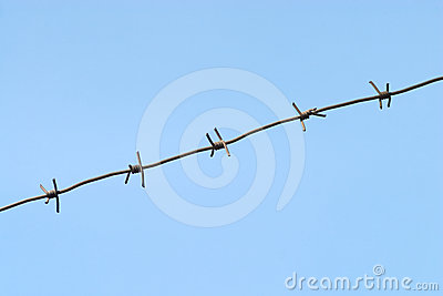 Gray barbed wire isolated on blue