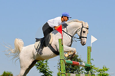 Gray horse and rider over a jump