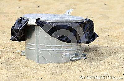 Gray metal garbage bin or can on beach