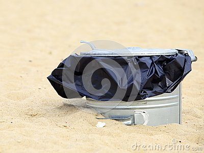 Gray metal garbage bin or can on beach