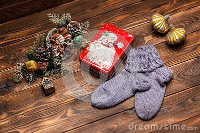 Gray woolen knitted socks, Christmas decorations and a metal box with the image of Santa Claus on a wooden background Stock Photo