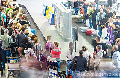 Lots of people getting luggage at airport. Editorial Stock Image