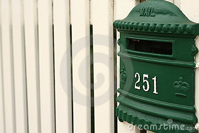 Greean mailbox on white picket fence