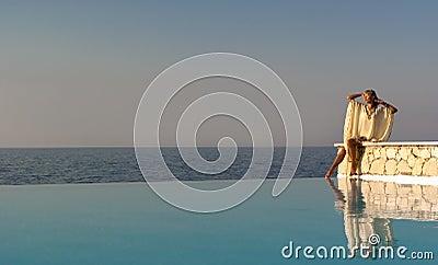 Greek style woman sitting on edge of infinity pool