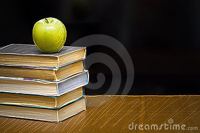Green apple on the  book. Blackboard with sign.