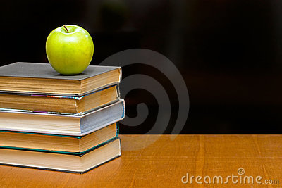 Green apple and  books on the desk.