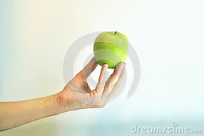 The green apple is in the fingers against colour b
