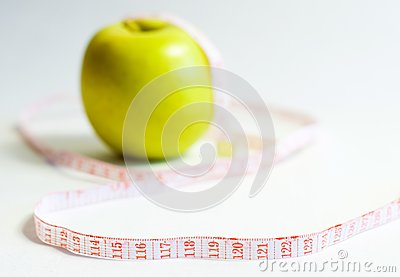 Green apple and measure tape, dieting theme