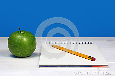 Green apple and notebook with pencil on white wooden desk