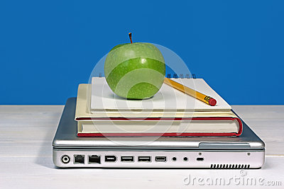 Green apple, pencil and book on laptop