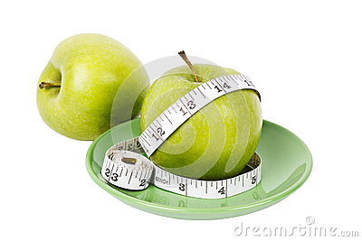 Green apples with measuring tape on green plate
