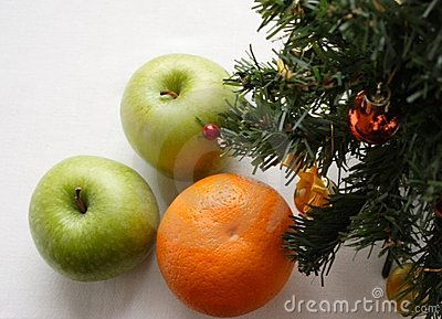 Green apples and orange under a New Year tree