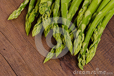 Green asparagus on brown wood