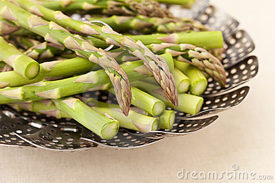 Green asparagus in steamer basket