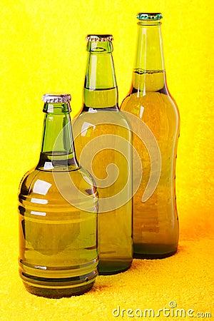 Green beer bottles against yellow