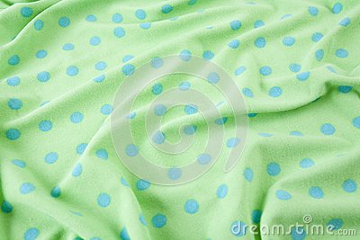 Green with blue polka dots wrinkled fabric