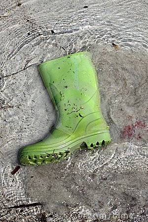 Green boots trash on beach shore pollution