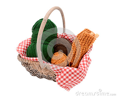 Green, brown and orange yarn with knitting in a basket