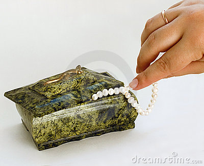 Green Casket hand taking pearl necklace from it