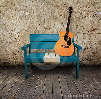 Green chair and acoustic guitar in a grunge room