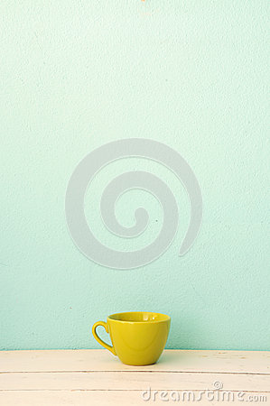 Green coffee cup on the white wood