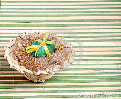 Green Easter egg in a straw hat