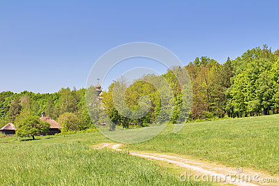 Green field, blue sky and old wooden chapel