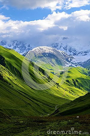 Free Green Fields And Hills Leading To Snow-covered Mountains Stock Photo - 104165040