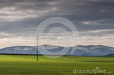 Green fields of cereal and mountains on a cold morning with fog