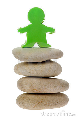 Green figurine on a stack of pebbles