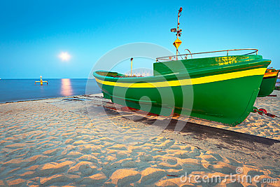 Green fishing boat on the beach of Baltic sea