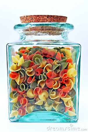 Green, glass, see through jar with cork lid containing colorful pasta shells.