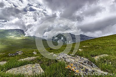 Green Grass Field With Rocks Near Mountains During Cloudy Daytime Sky Free Public Domain Cc0 Image
