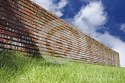 Green grasses and brick wall over blue sky