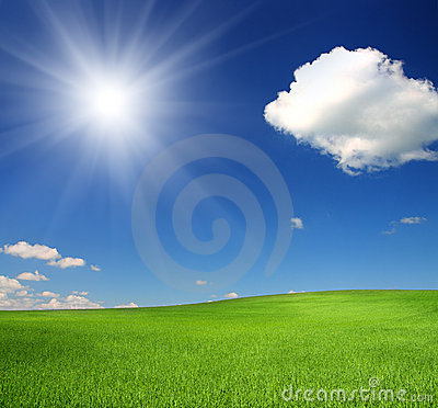 Green hill under sky with sun