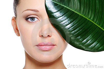 Green leaf shading a beautiful female face
