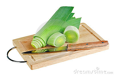 Green leek with knife on wooden chopping board