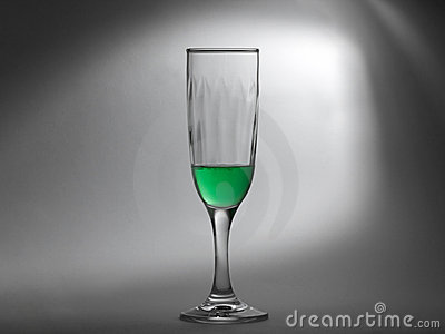 Green liquid in a glass cup on greyish background