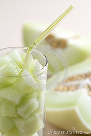 Green melon pieces in a glass with straw