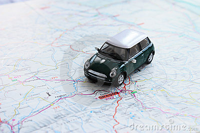 Green miniature car on paper map