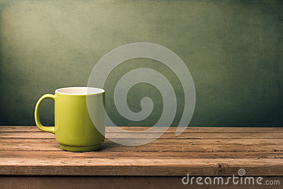 Green mug on wooden table